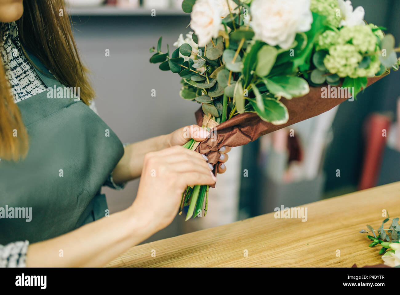 Female florist decorate fresh flower composition - Stock Image