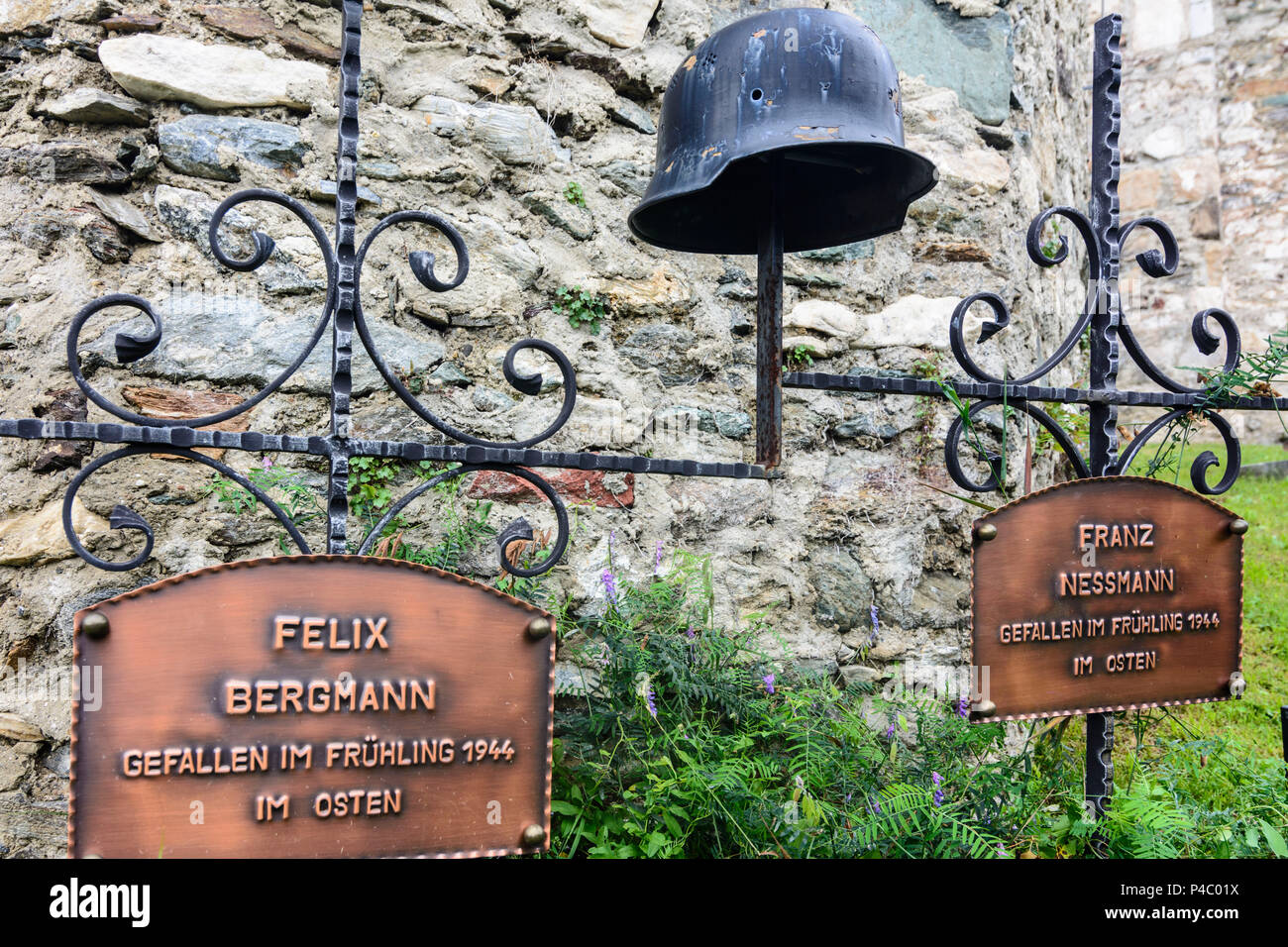 Maria Saal, grave crosses for soldiers died 2nd world war at eastern front, combat helmet with bullet hole, at church wall in Karnburg, Kärnten, Carinthia, Austria - Stock Image