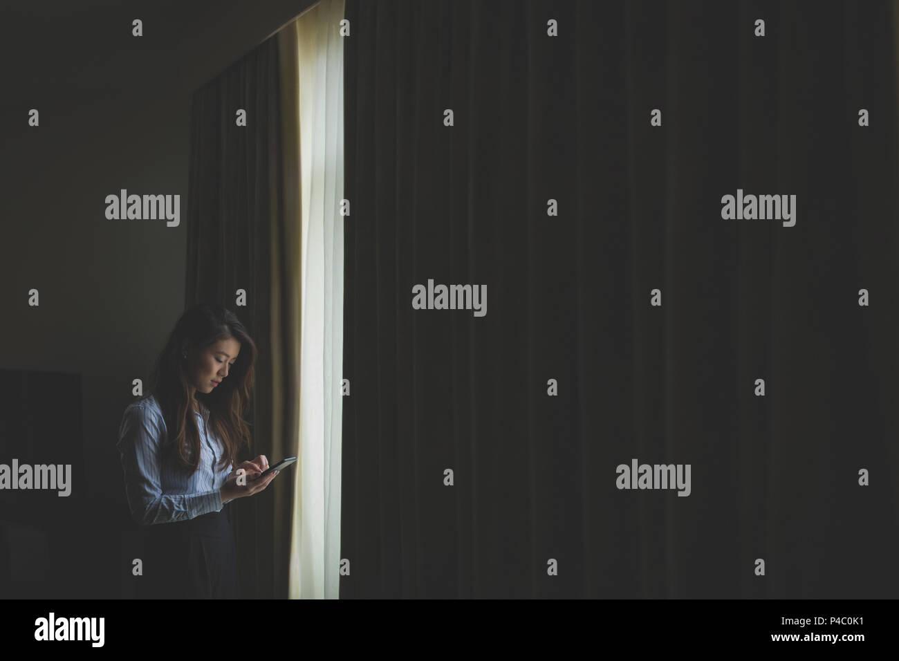 Businesswoman using mobile phone - Stock Image