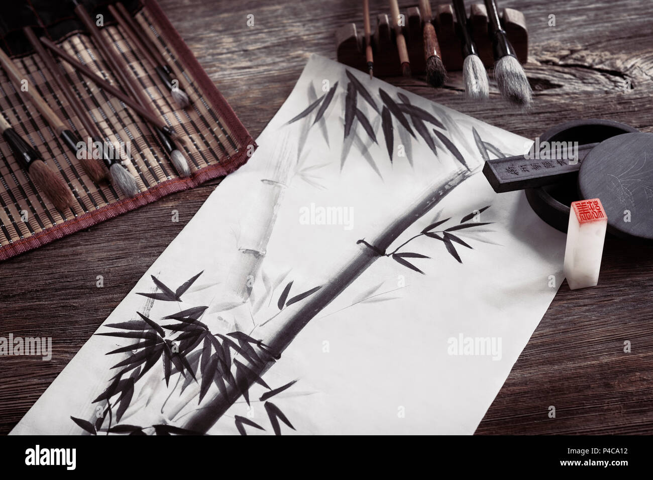 Japanese sumi-e painting of a bamboo on rice paper and artist tools, brushes, ink stone and seal, artistic still life on rustic wood background - Stock Image