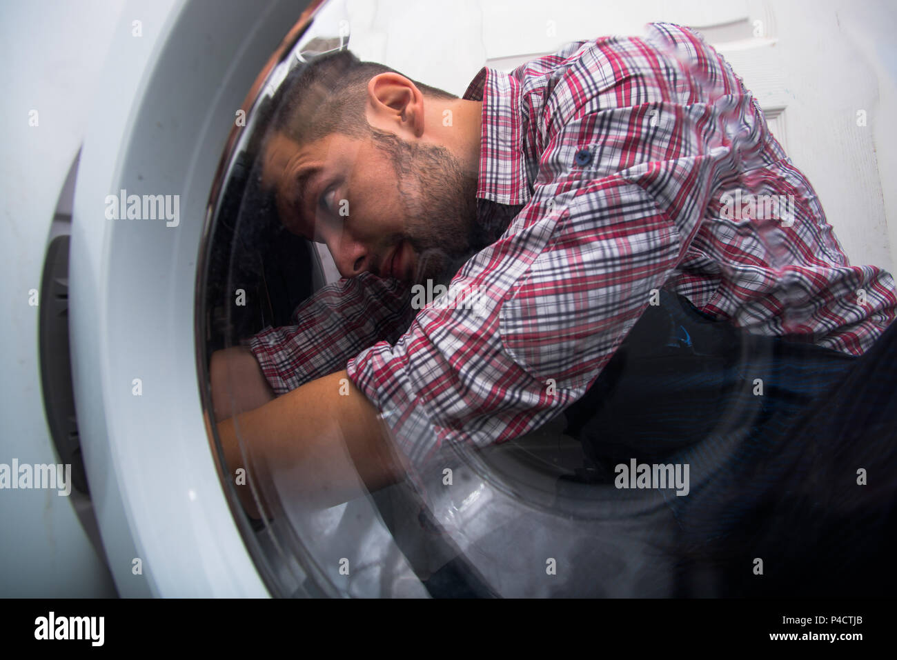 Repair man fixing the washing machine in the bathroom - Stock Image