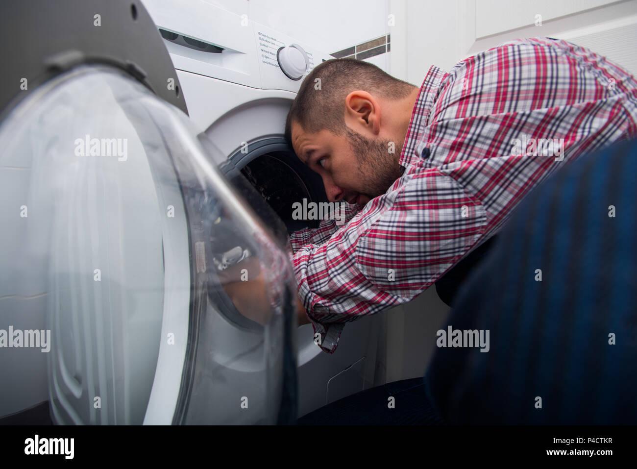 Repair man fixing the washing machine in the bathroom - Stock Image
