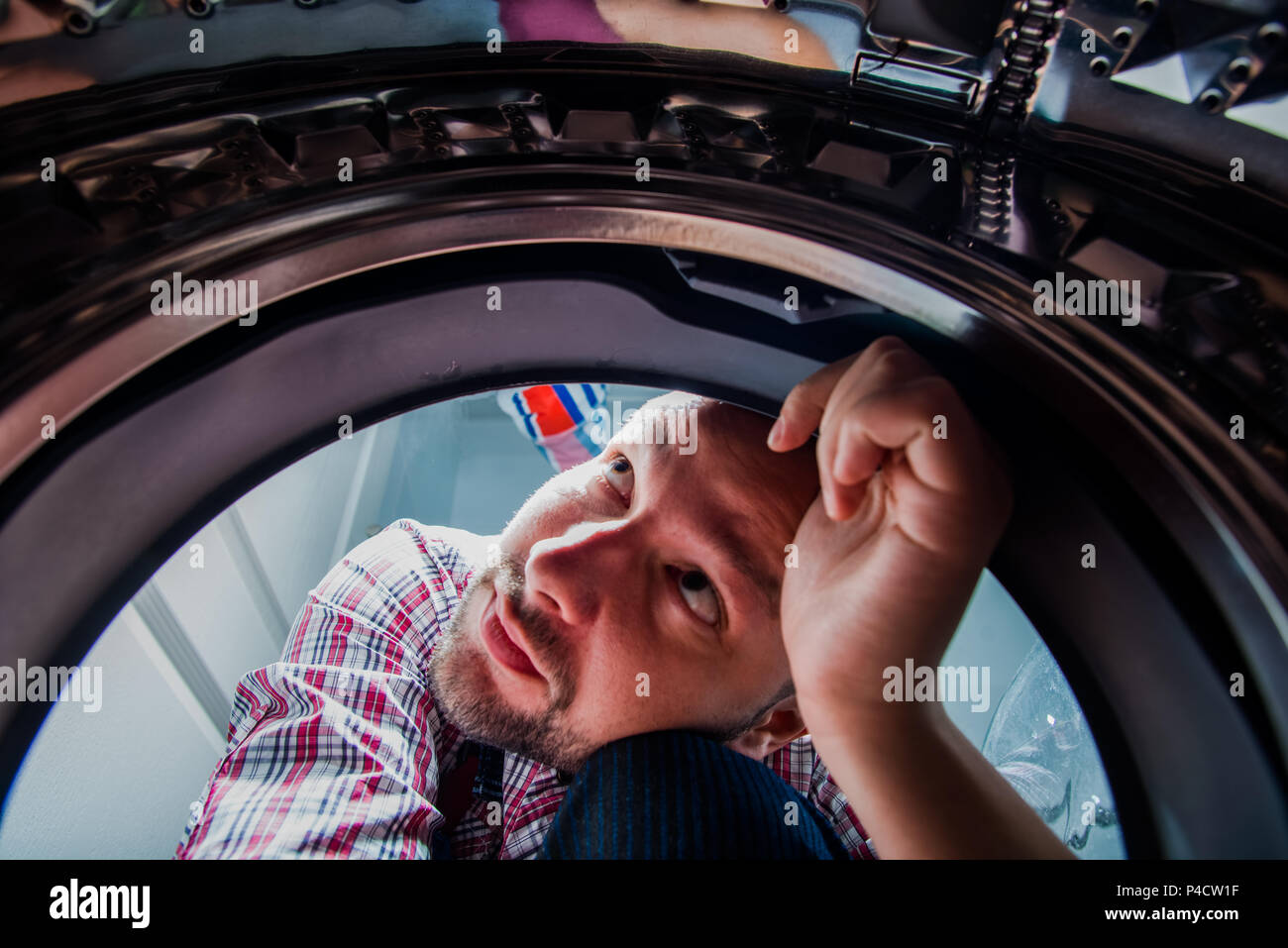 Repair man fixing the washing machine in the bathroom, view from inside the machine - Stock Image