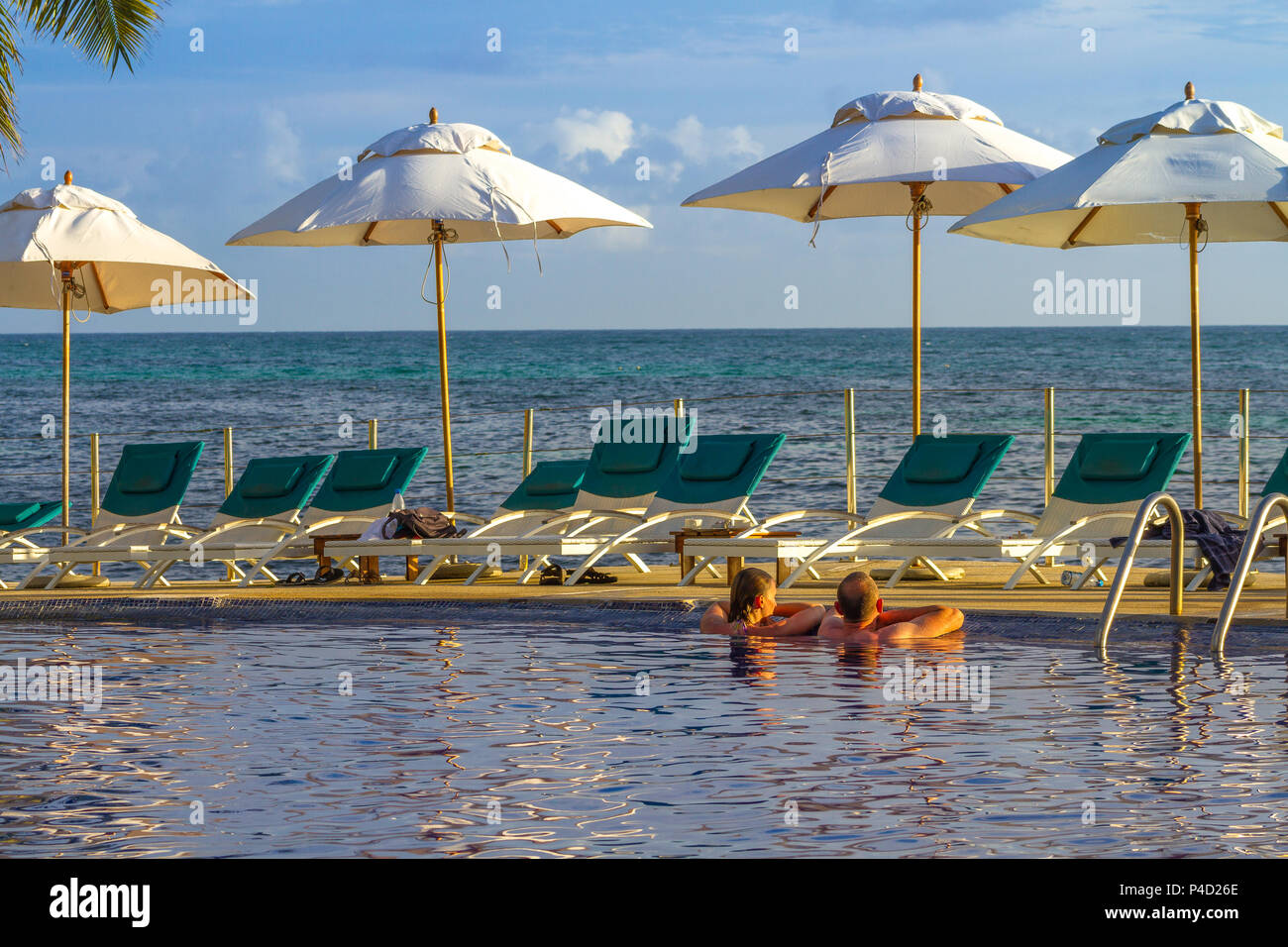 Praslin, Seychelles - unidentified guests at the Hotel Coco de Mer relax in a seaside pool image with copy space in landscape format - Stock Image