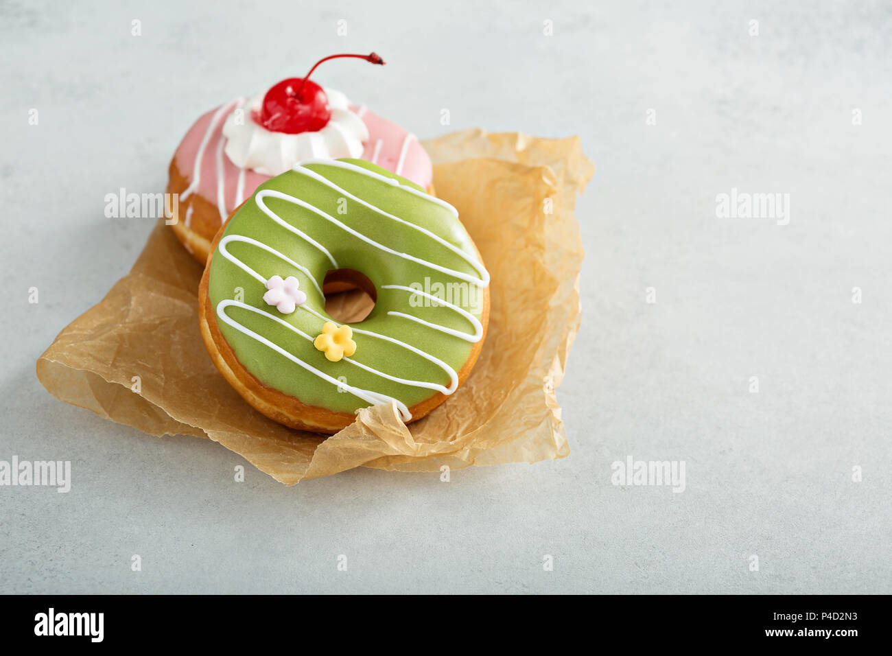 Assorted glazed fried donuts on parchment Stock Photo