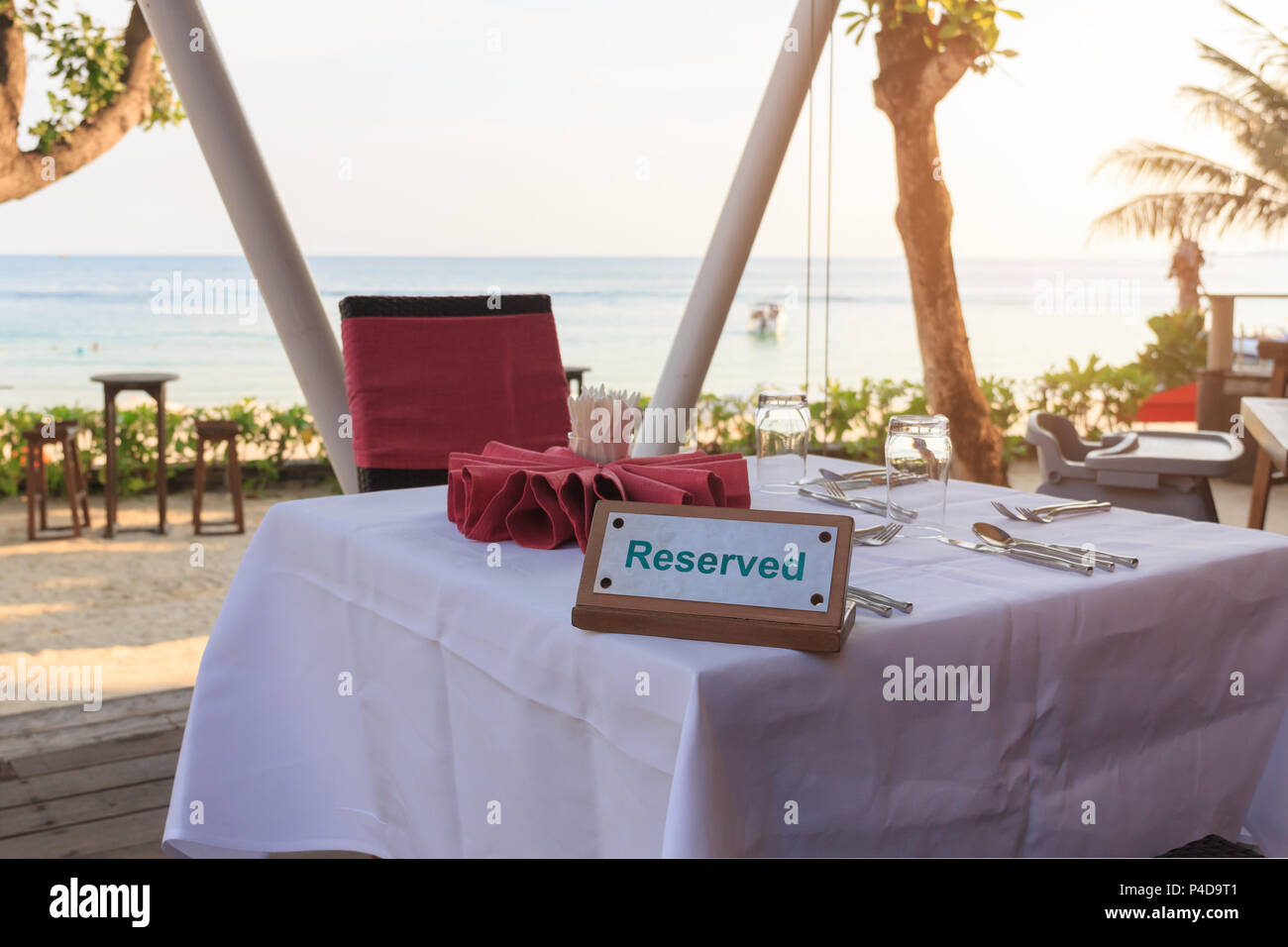 Reserved table dinner time in luxury restaurant on sea background. - Stock Image