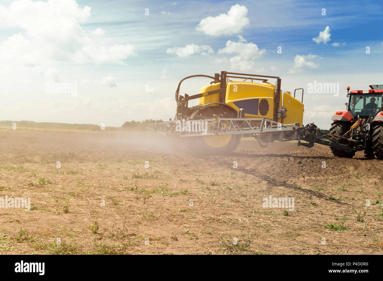 Tractor with sprayer trailer beside the cereal field. Heavy machinery for agriculture - Stock Image