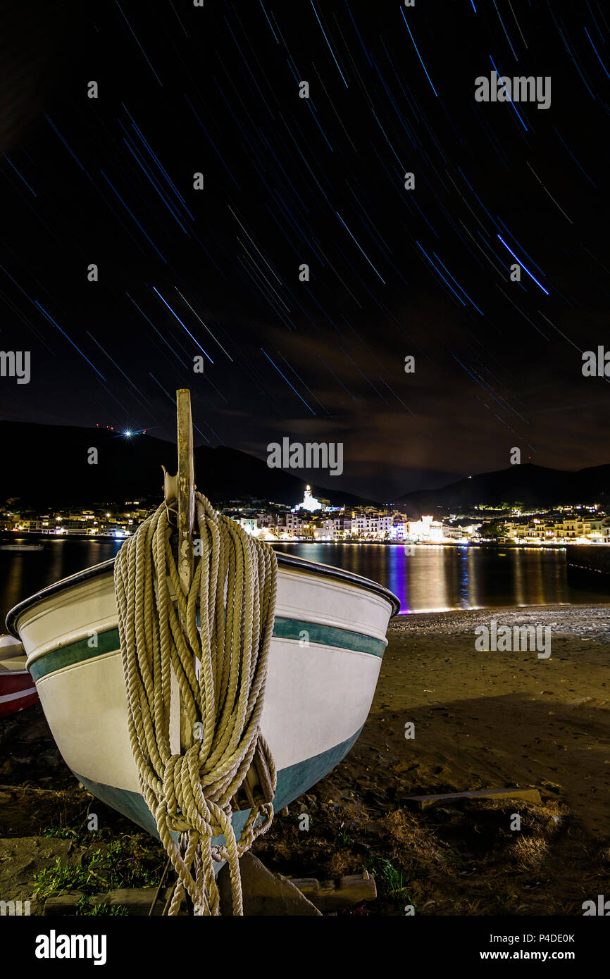 A view of the town of Cadaqués under the star trails, Catalonia, Europe. - Stock Image