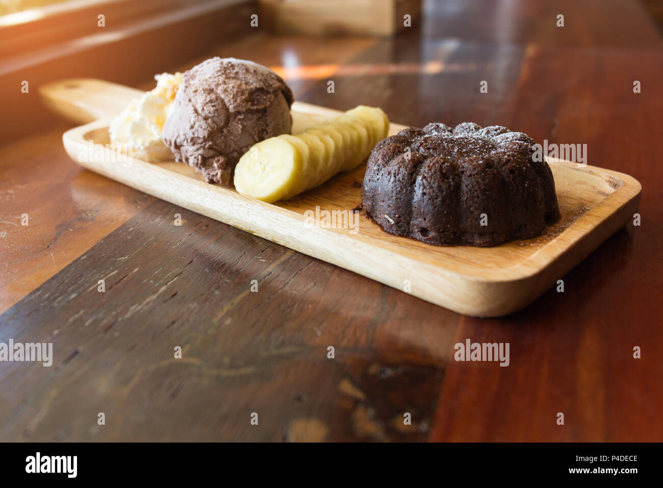 Chocolate lava cake set, with chocolate icecream banana apple fruit and whipped cream on wood table in the cafe, dessert summer. - Stock Image