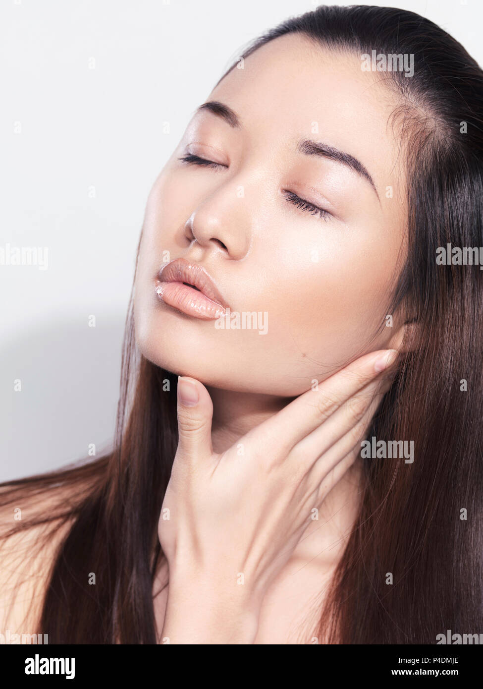 Closeup beauty portrait of an asian young woman face with light porcelain or glass skin - Stock Image