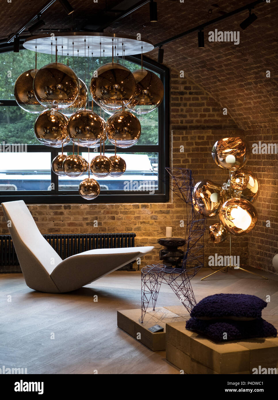 Cluster of Tom Dixon metallic pendant lights hanging in front of a window at the Tom Dixon flagship store and showroom at Coal Drops Yard, Kings Cross - Stock Image