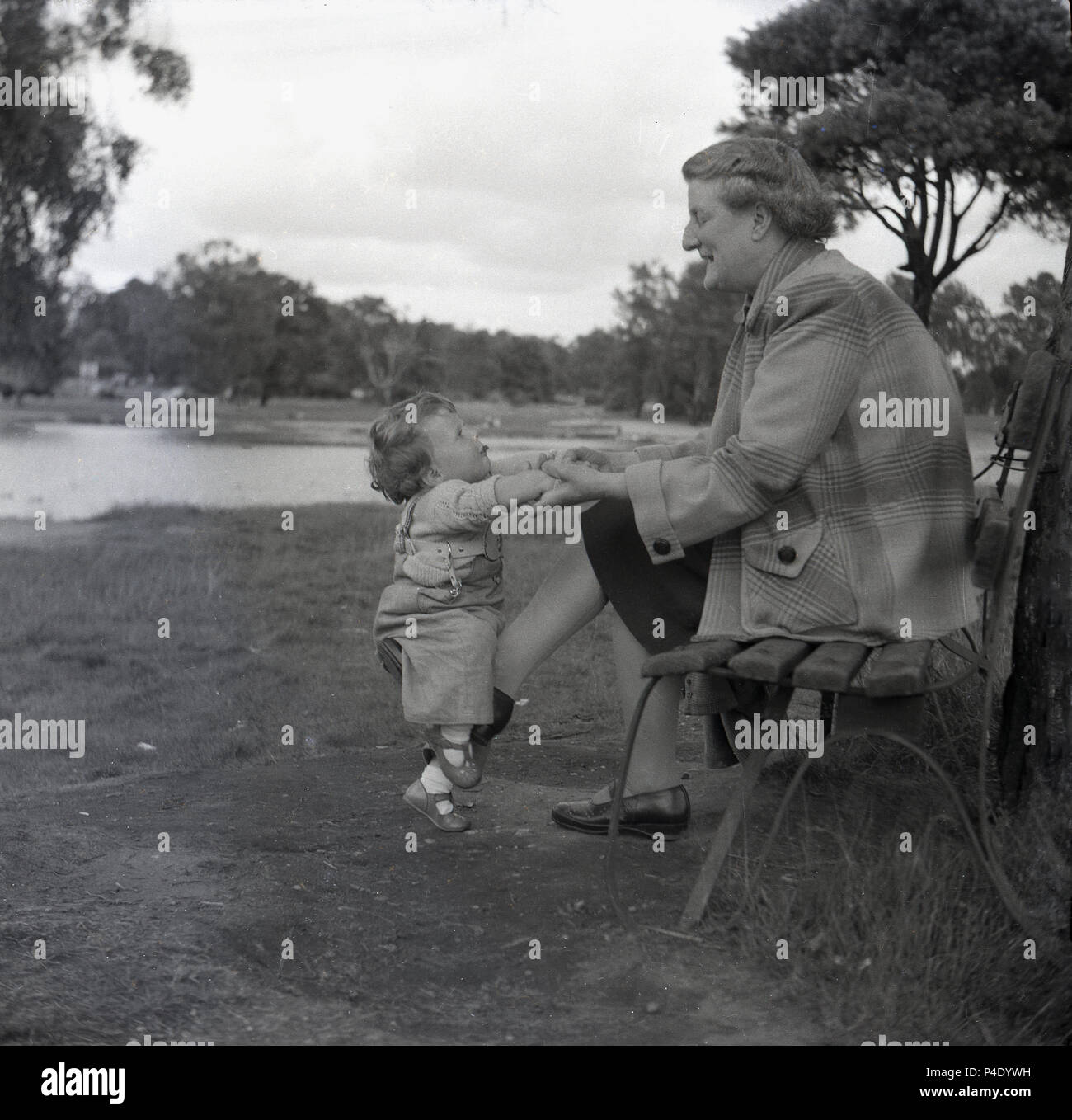 1950s, historical. a grandmother sitting on a bench playing with her infant granddaugher outside in a park. In this post-war era in Britain, the grandparents had a big role tp play in infant childcare as creches, nursery and pre-schools were not fully established. - Stock Image