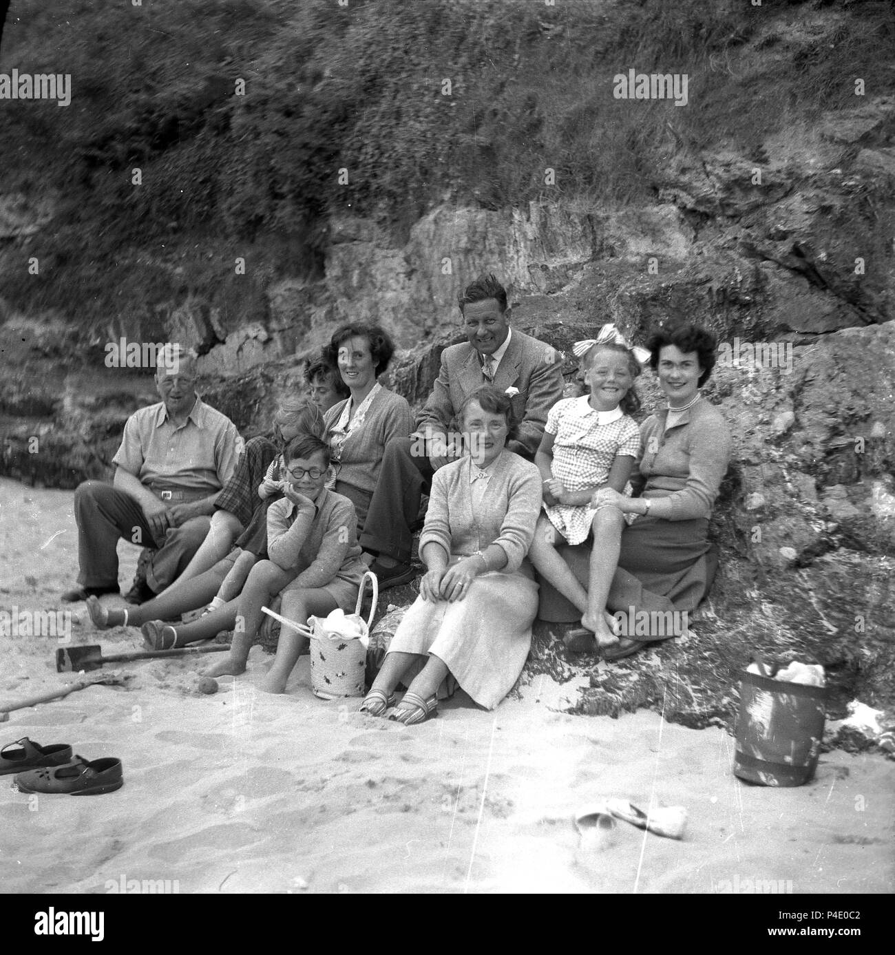 1950s, group family photo by some rocks on the edge of the beach, England, UK. In this post-war era it was common for different generations to go away to the seaside together. - Stock Image