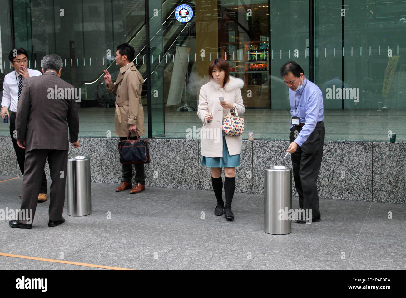 Japanese people smoke cigarettes in a special  smoking area on the street of Tokyo, Japan – jan, 24, 2011. Stock Photo