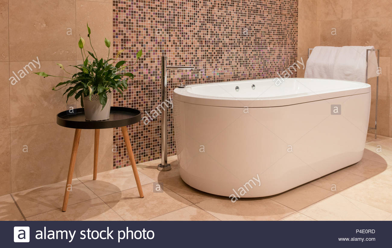 Stone tiles. Bath tub and mosaic tiles feature in this modern ...