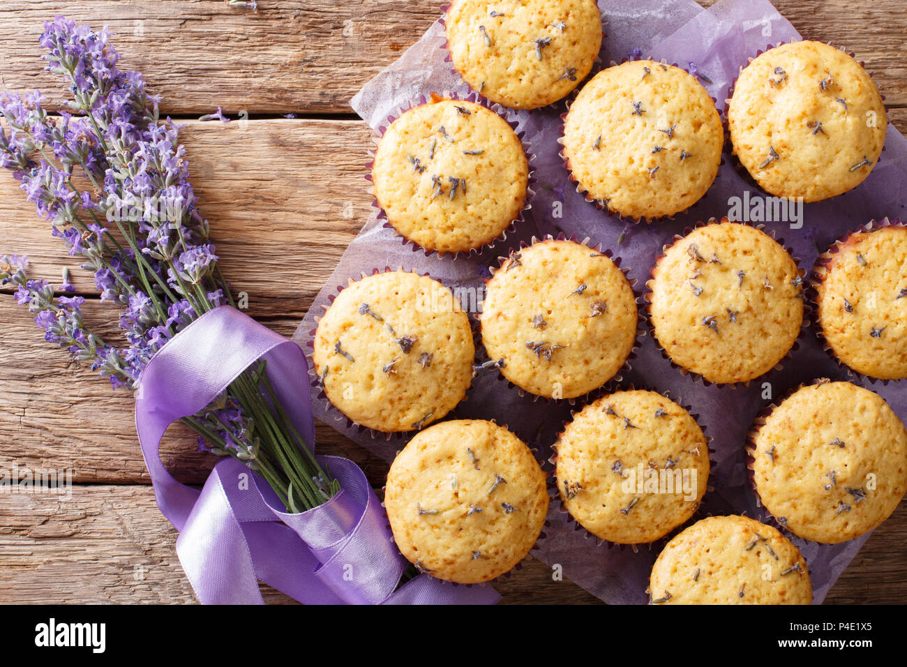 Beautiful food dessert: muffins with lavender flowers close-up on the table. Horizontal top view from above - Stock Image