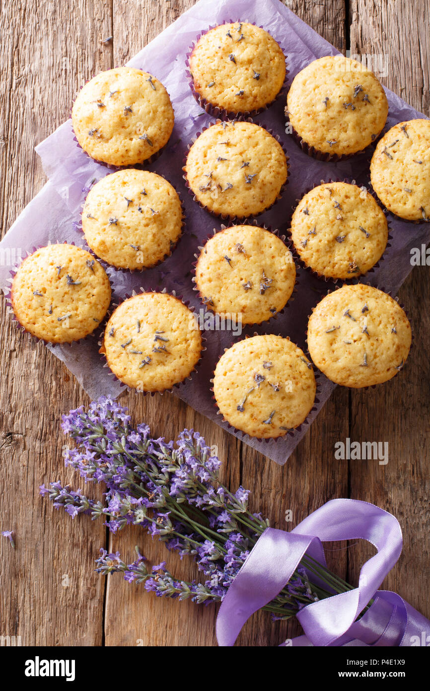 Beautiful food dessert: muffins with lavender flowers close-up on the table. Vertical top view from above - Stock Image