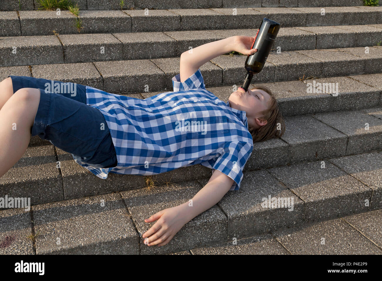 underage boy drinking whine (the scene is being acted) - Stock Image