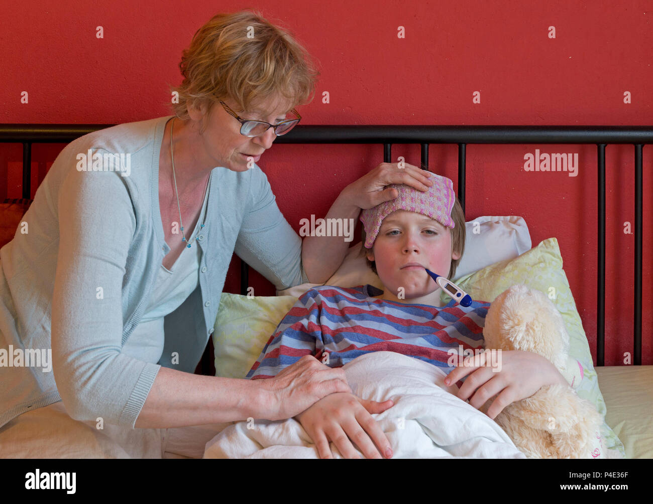 mother comforting her ill son in his bed Stock Photo