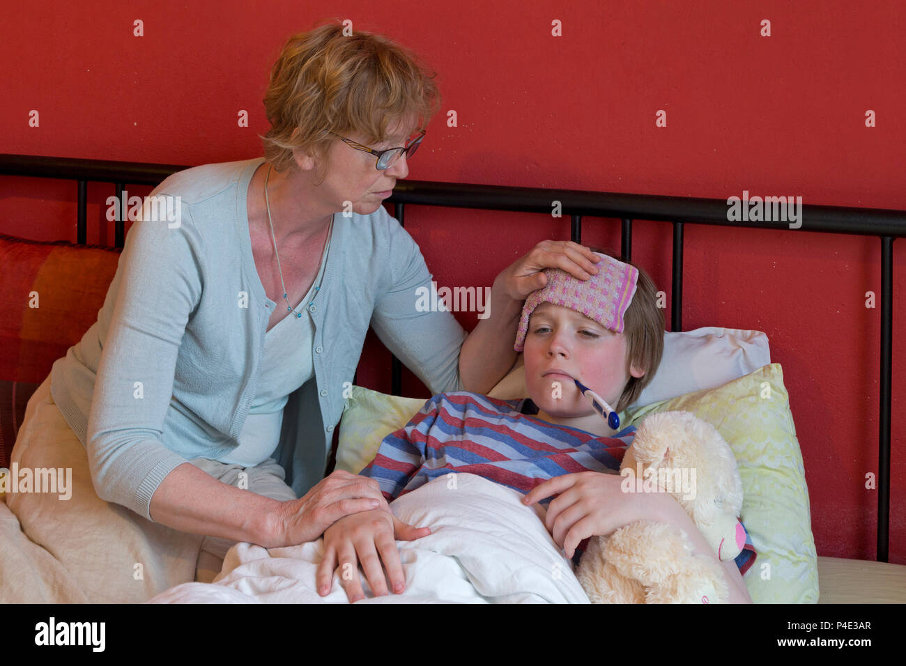 mother comforting her ill son in his bed - Stock Image
