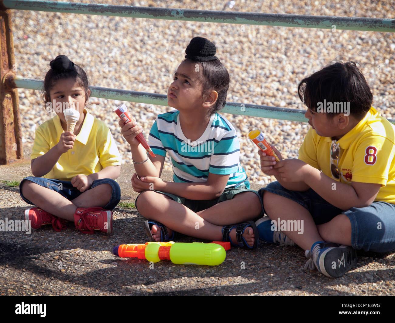Young Asian boys enjoying ice creams close to Brighton beach