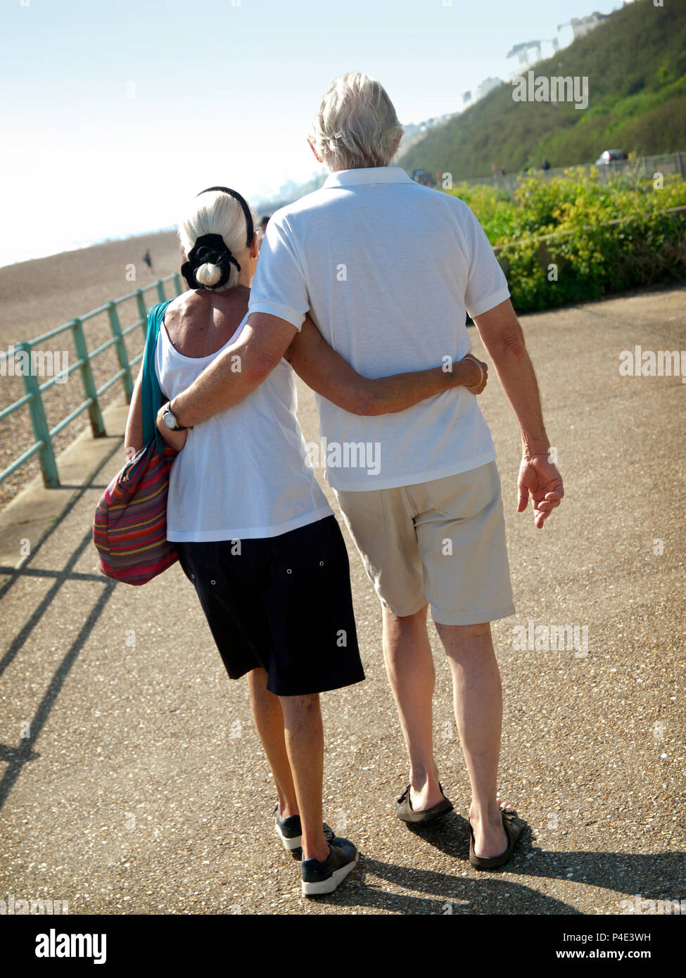 A mature couple stroll arm in arm near to the beach at Brighton - Stock Image