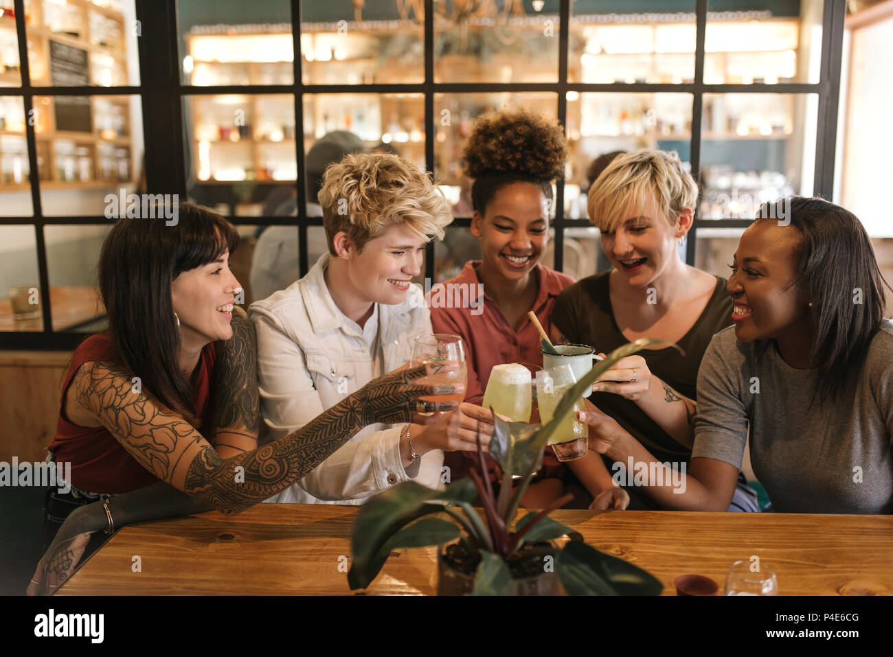 Diverse girlfriends toasting together at a trendy bistro table - Stock Image