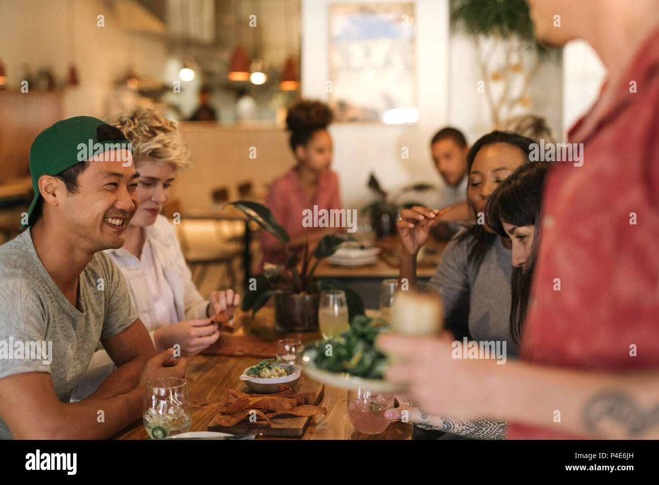 Smiling young friends enjoying themselves while sitting in a bistro - Stock Image