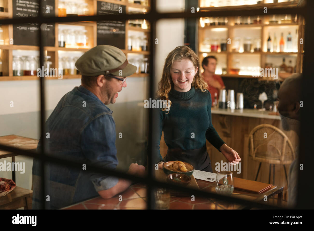 Smiling waitress serving food to a bistro customer - Stock Image