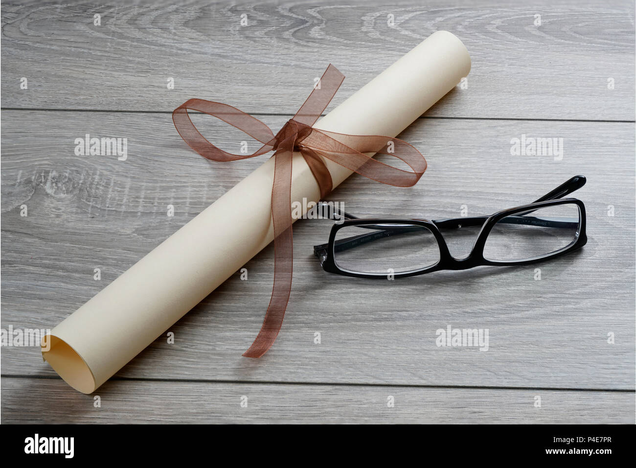 a diploma rolled up and tied with a red ribbon on the table with a pair of glasses - Stock Image