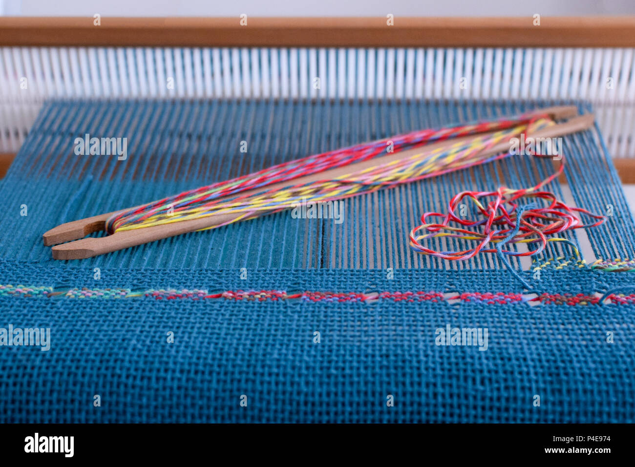 Spanish lace weaving on rigid heddle loom with blue warp and colorful weft - Stock Image