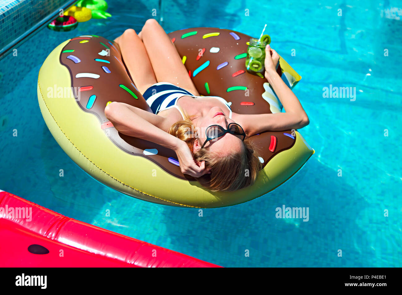 Young woman on summer pool party in swimming pool drinkig lemonade ...