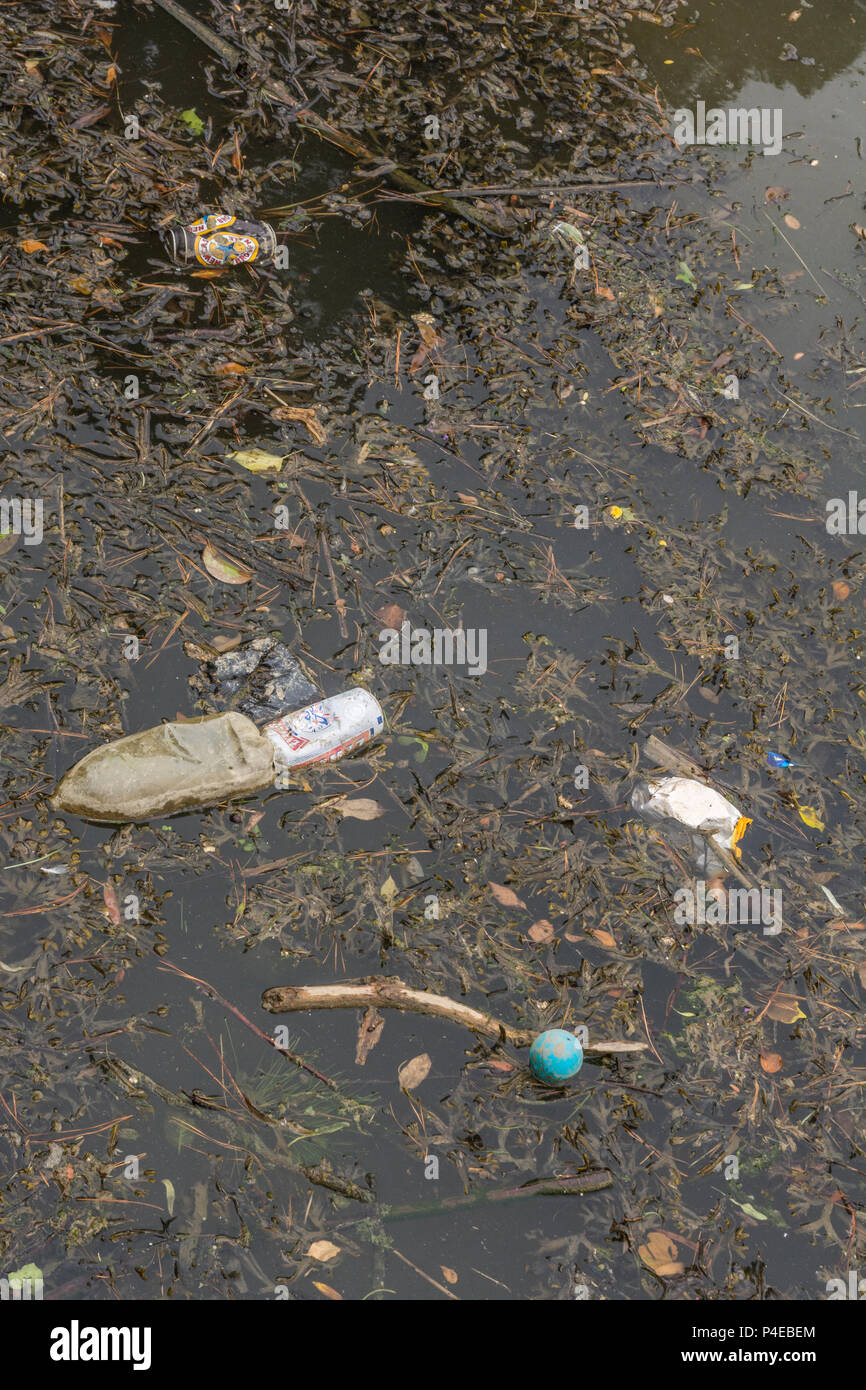 Plastic pollution in the river at Truro, Cornwall. Metaphor war on plastic, plastic rubbish. - Stock Image