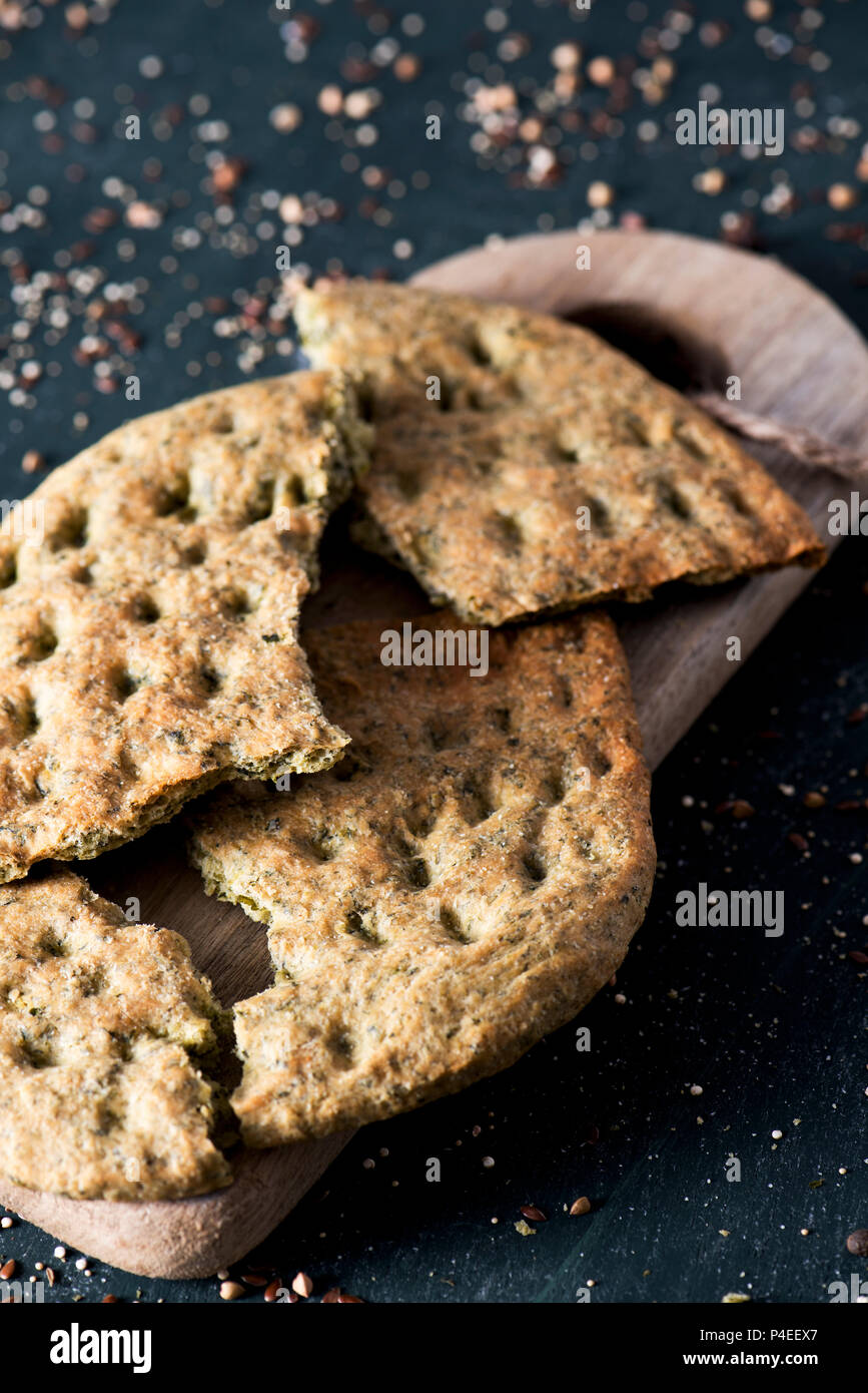 closeup of a kale flatbread, broken in some pieces, on a chopping board, placed on a dark green rustic wooden table Stock Photo