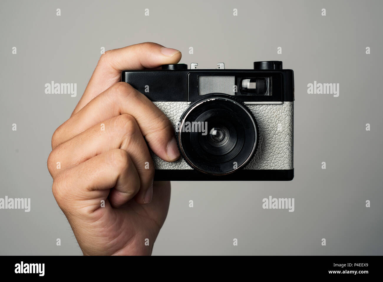 closeup of a caucasian man with a retro film camera in his hand, pointing to the obserever, about to press the shutter button, against an off-white ba - Stock Image