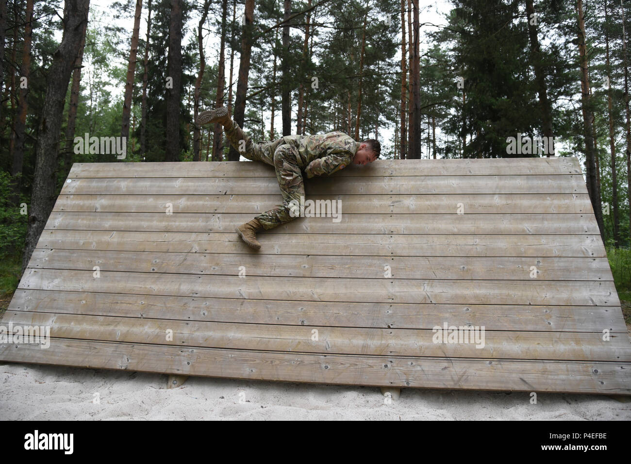 U.S. Army Spc. Derek Teegardin with 1st Battalion, 4th Infantry Regiment, Joint Multinational Readiness Center, 7th Army Training Command (7ATC), jumps over a slanted wall at the obstacle course as part of the 7ATC Best Warrior Competition June 19, 2018 at Grafenwoehr Training Area, Germany. Teegardin, a Battle Creek, MI native is competing in the three-day event ending June 21 with the announcement of the 7ATC Officer, Noncommissioned Officer and Soldier of the Year. The winners will move on to compete in the U.S. Army Europe Best Warrior Competition. (U.S. Army photo by Markus Rauchenberger) - Stock Image