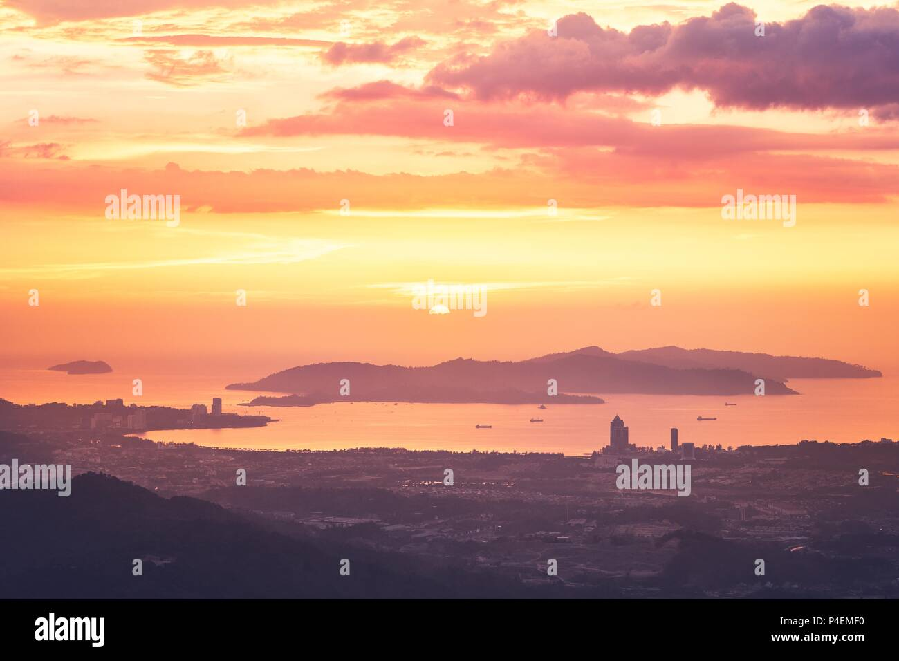 View of silhouette landscape with Kota Kinabalu city against islands at golden sunset.  Sabah state, Malaysia. - Stock Image