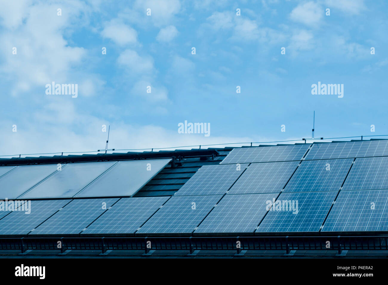 photovoltaic solar panel modules on the roof of a building to generate clean electric energy - Stock Image