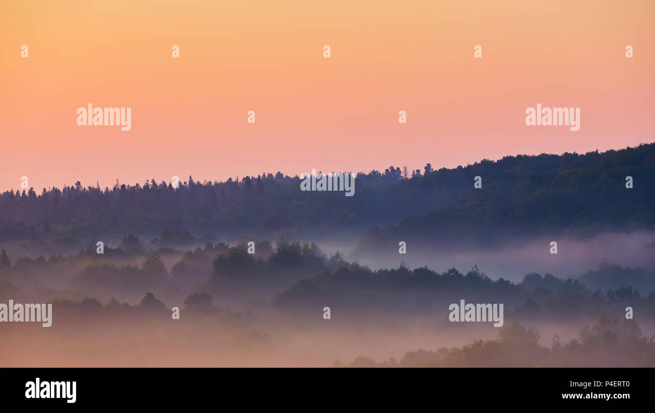 Misty morning of hilly area with ray of light. Stock Photo