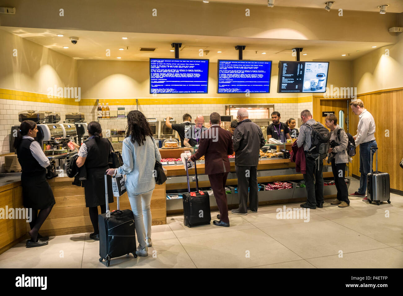 People buying fast food at counter with Windows blue screen on monitors, Heathrow, London airport, UK - Stock Image
