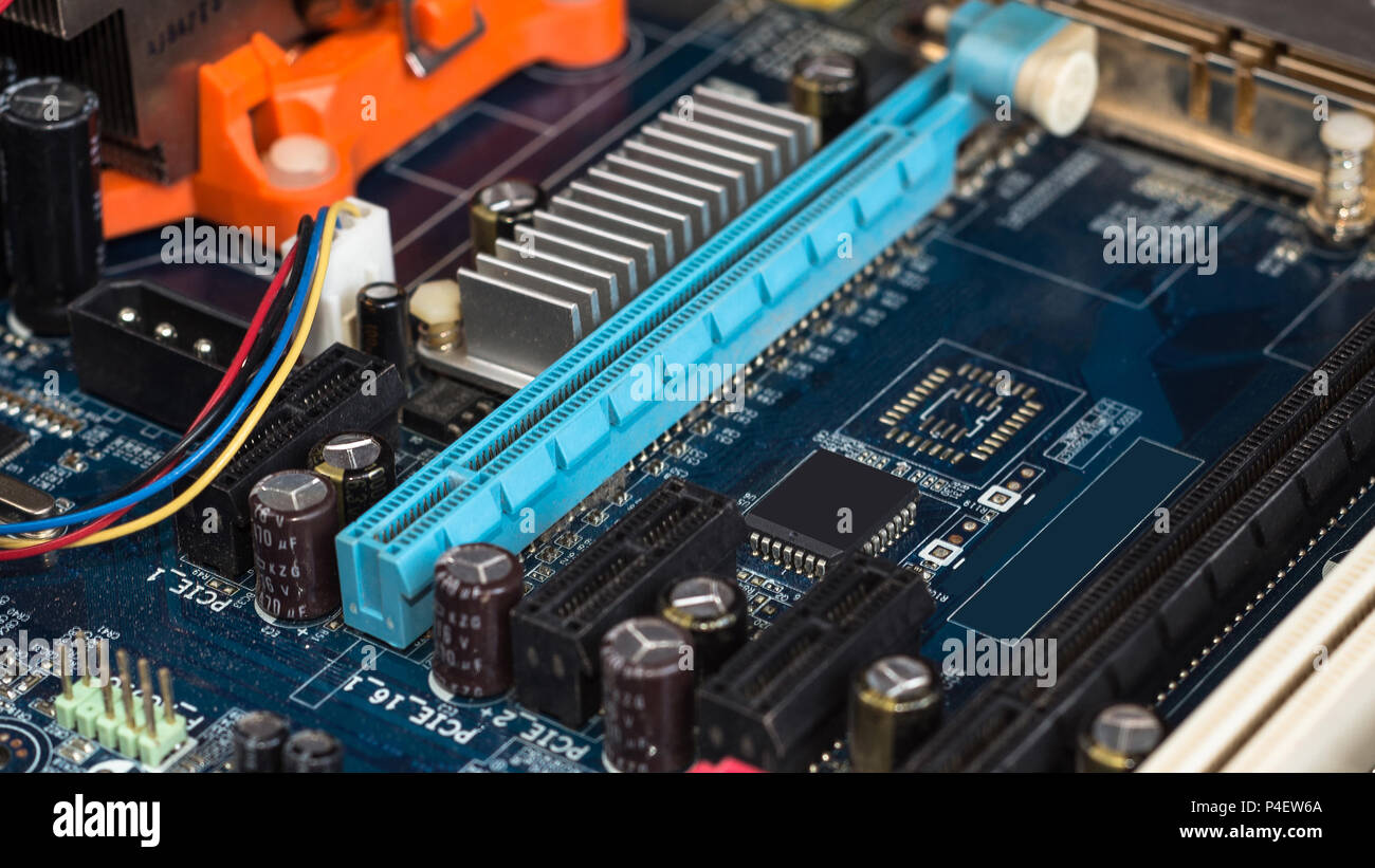 Motherboard with visible PCI express connector slot, heat sink, memory slot, cpu socket in blue. Stock Photo