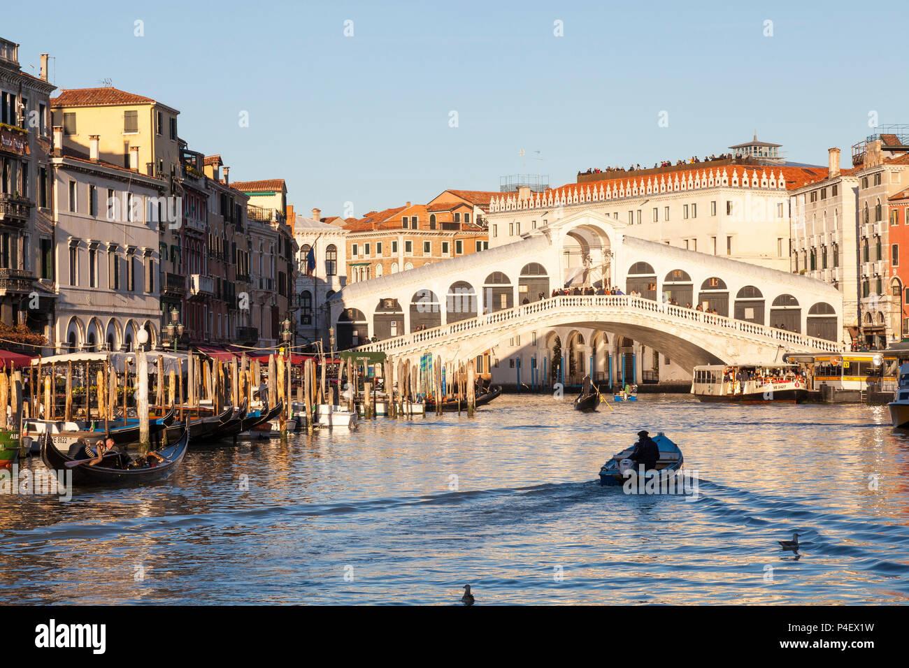 Rialto Bridge, Grand Canal, at sunset with gondolas and small boat with wake, Venice, Veneto, Italy - Stock Image
