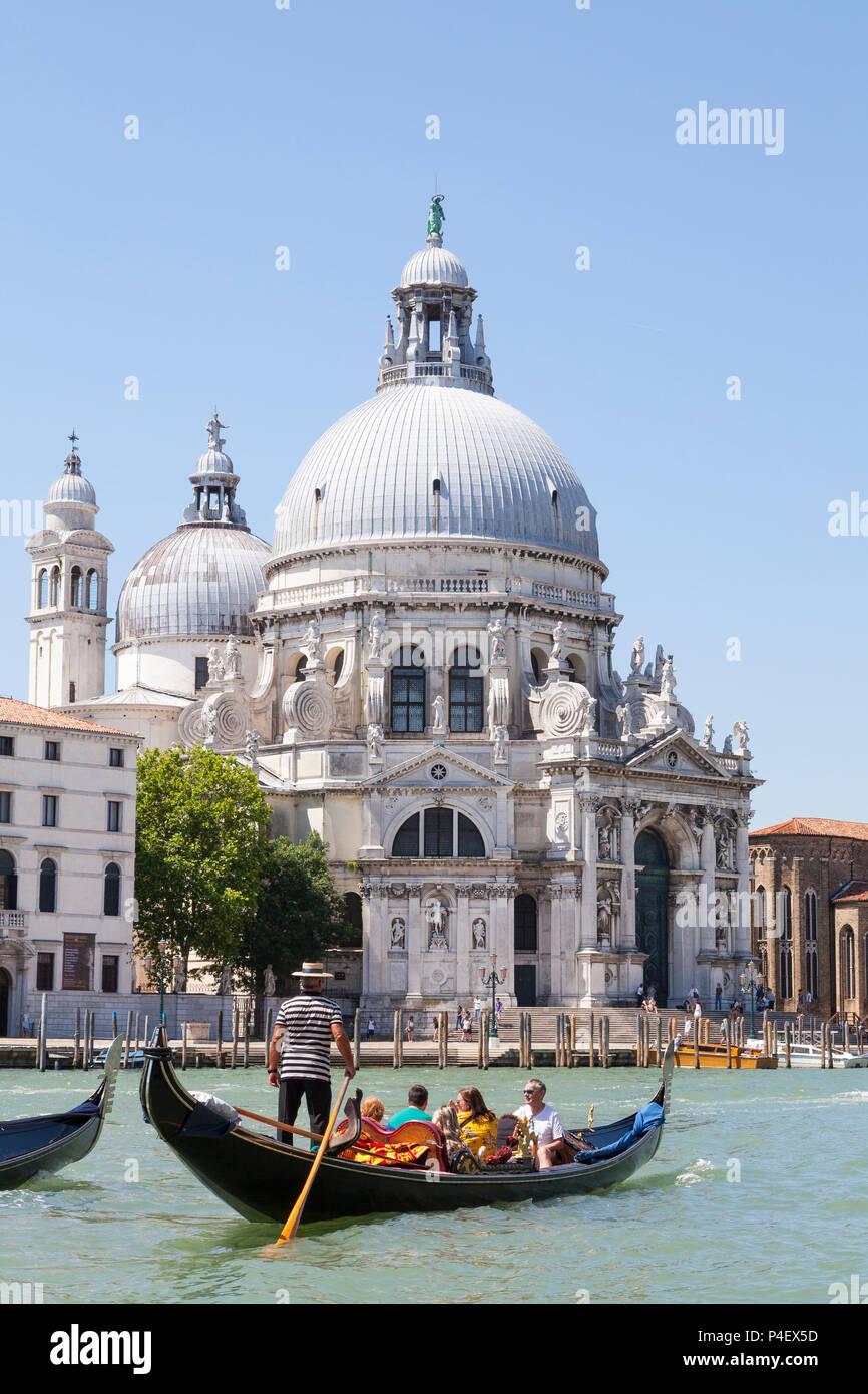 Gondolas  with tourists in front of the Basilica di Santa Maria della Salute, Grand Canal, Dorsoduro, Venice, Veneto, Italy in early morning light - Stock Image