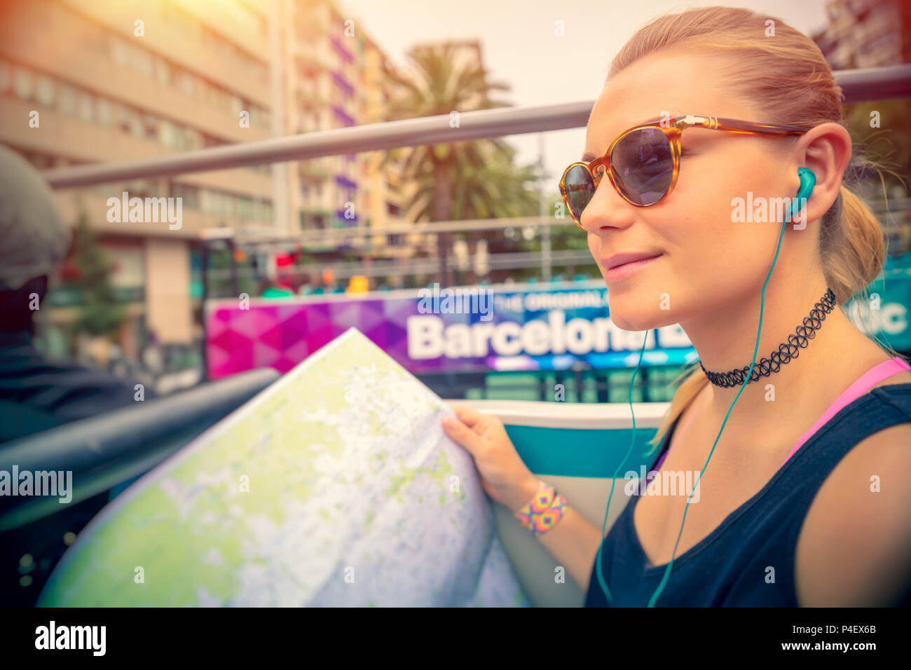 Cute blond woman riding on the bus with headphones in ears and with map in hands, discovering points of interest of Barcelona, active summer vacation  - Stock Image