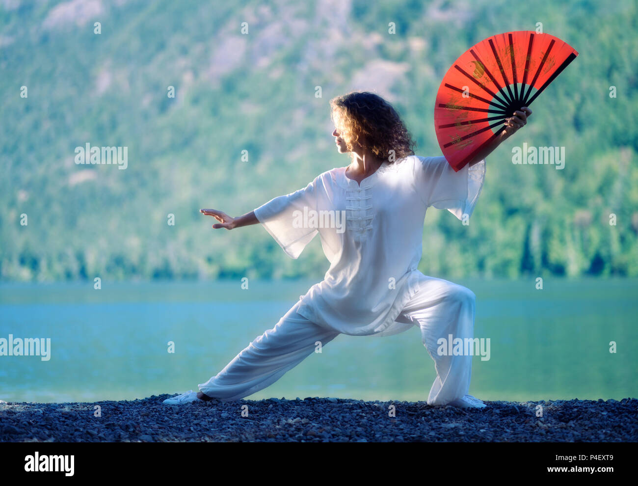 Young woman practicing Tai Chi Chuan with a red fan in the morning sunrise at a mountain lake shore in the nature - Stock Image