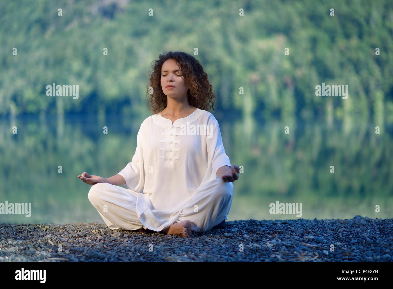 Young woman in white silk outfit meditating in the morning sunrise by the lake in the nature - Stock Image