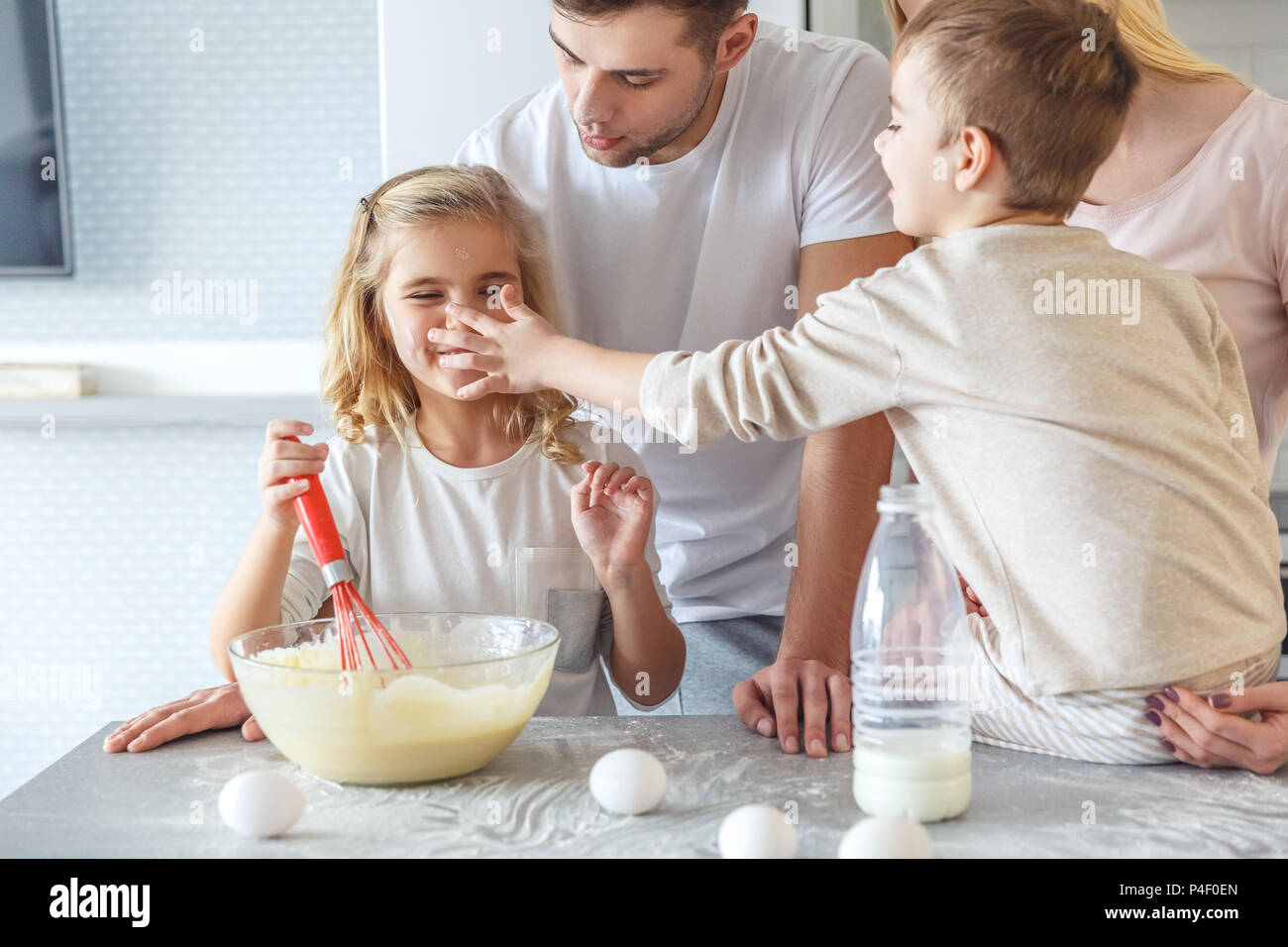 young family playing while cooking breakfast together - Stock Image