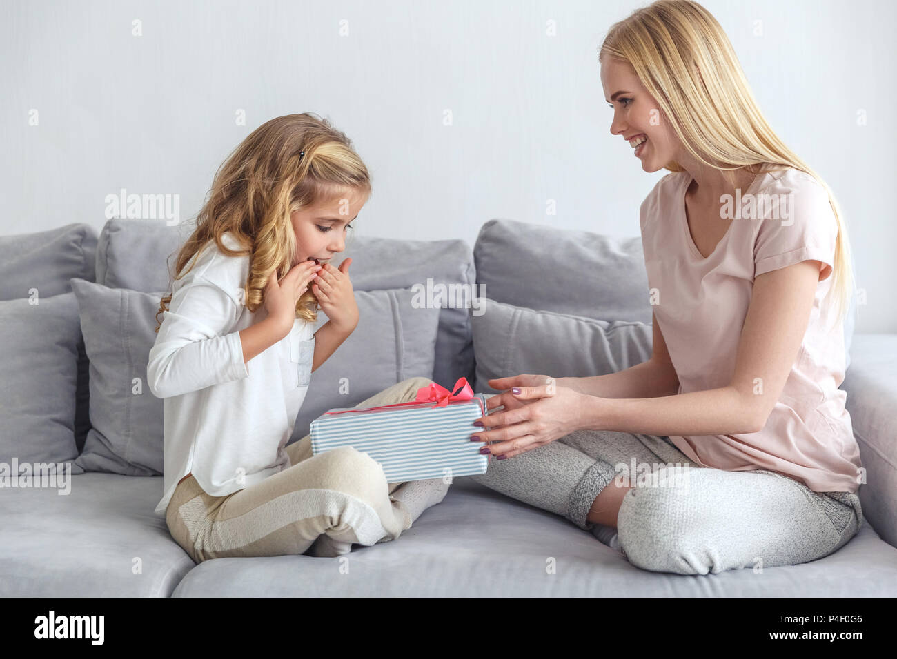 Mother Presenting Birthday Gift For Surprised Little Daughter