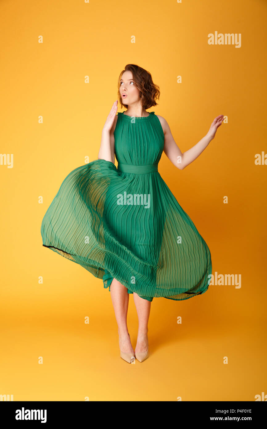 19cdcdef6634 young beautiful woman in green dress with oops gesture isolated on orange -  Stock Image