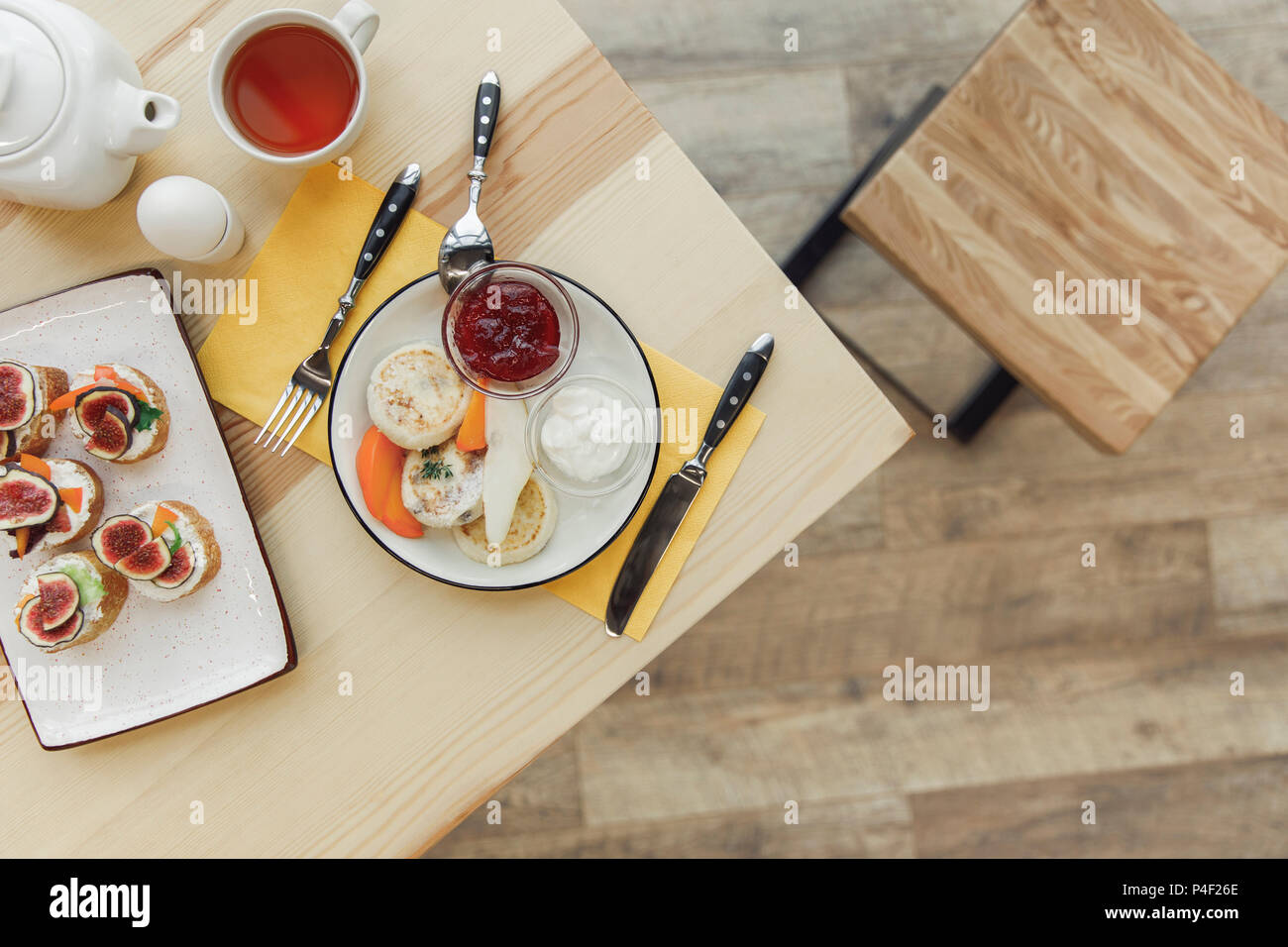 top view of healthy delicious breakfast with tea set on wooden table - Stock Image